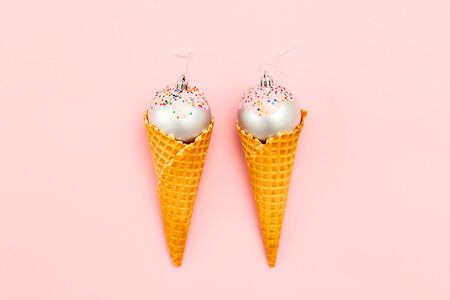 Two Christmas ball sweet in waffle cone on pink background.  Flat lay 写真素材