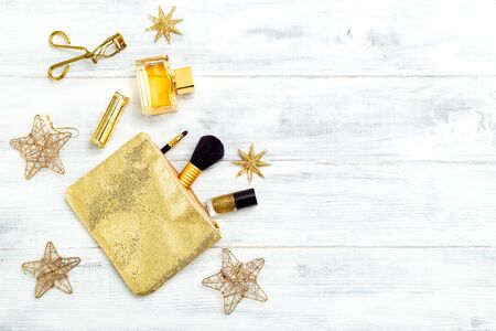 Christmas golden make up on white wooden background. Copy space