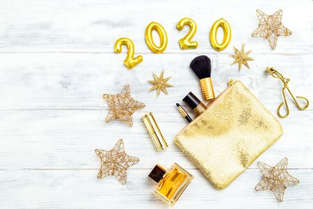 Make up golden color and 2020 golden number on white wooden background. Copy space