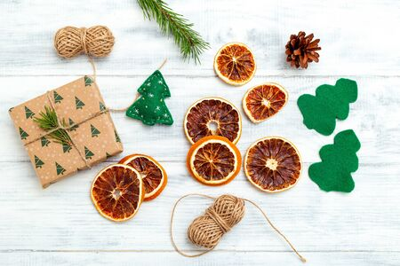 Christmas decorations. Felt tree green and dried orange on white wooden background. Flat lay