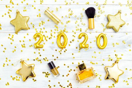Make up golden color and 2020 golden number on white wooden background. Flat lay Imagens