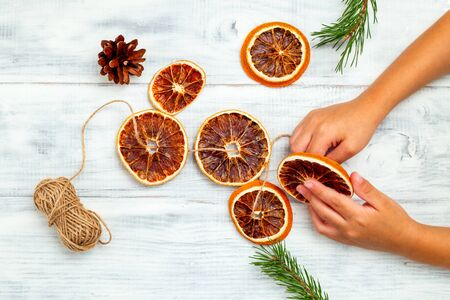Christmas decorations. Hands Doing Christmas Garland Crafts Dried Orange Slices. Flat lay 写真素材
