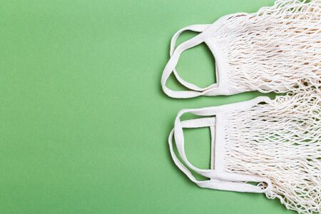 Two Mesh shopping bag on green background. Copy space. Reusable bag 写真素材