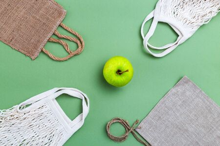 Reusable bags and green apple on green background. Zero waste. Flat lay