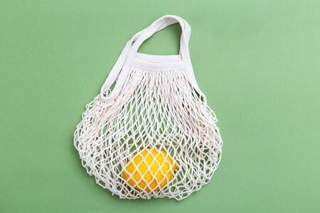 Mesh shopping bag with lemons on green canvas background. reusable concept. BACK TO NATURE
