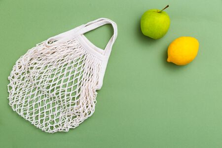 Mesh shopping bag on green background. BACK TO NATURE. Copy space 写真素材