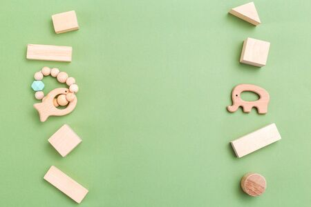 Baby developing wooden toys on green background. Copy space