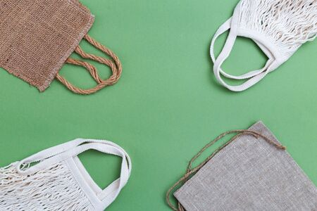 Reusable bags  on green background. Zero waste. Copy space
