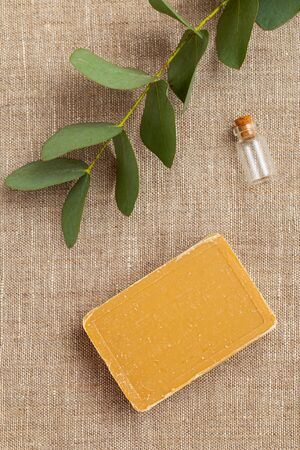 Sprig of eucalyptus and natural soap on a linen background. Vertical