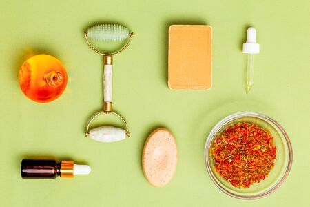 Herbs and oil on green background. Modern apothecary. Flat lay Imagens - 134805011