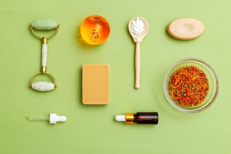 Herbs and oil on green background. Modern apothecary. Minimalist style Imagens