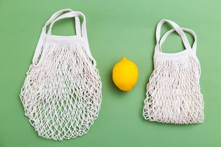 Reusable mesh bags with lemon on green background. Flat lay Imagens