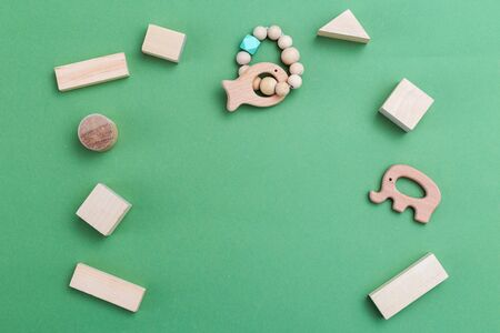 Organic wooden baby toys on green background. Copy space