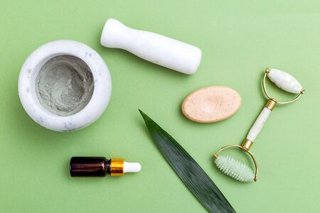 Face roller and organic beauty product on green background. Minimaliost lifestyle