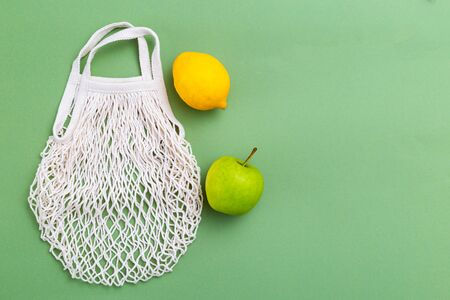 Reusable mesh bag with fruits on green background. copy space