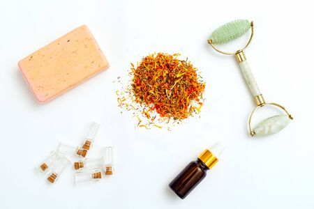 Dried marigold flowers and face roller on white background. Apothecary Imagens