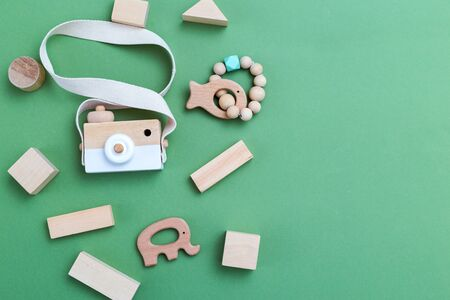 Wooden organic toys on  green background. Copy Space
