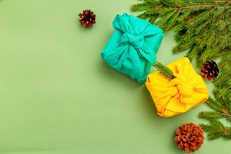 Furoshiki christmas gift and organic christmas decoration on green background. Copy space