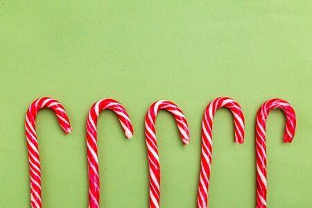 Christmas candy cane on green background. Copy space