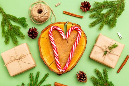 Heart made candy cane and organic christmas decoration on green background. Flat lay Imagens