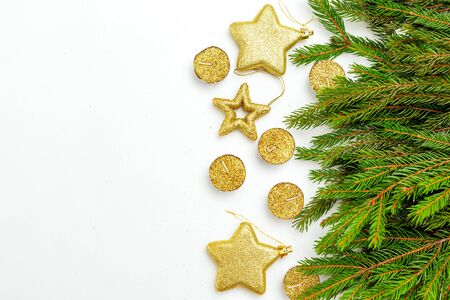 Golden candles and  stars gold colors  with green Christmas tree branches on white background. Copy space Imagens - 134805071