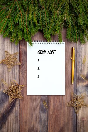 Goal list. Notepad and golden stationary on wooden background. Christmas accessories