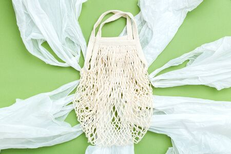 Reusable mesh bag  with plastic alternatives  on green background. Reusable concept. Flat lay