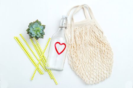 Reusable bottle and reusable mesh bag on white background. Sustainable lifestyle. Succulents plants Imagens