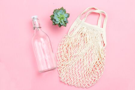Reusable bottle and reusable mesh bag on pink background. Sustainable lifestyle. Succulents plants Imagens
