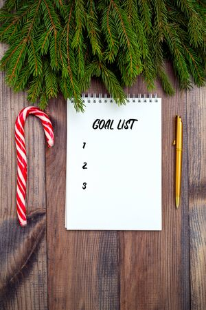 Goal planning. Notepad and golden pen  and candy cane on wooden background. Christmas accessories Banque d'images - 134805078