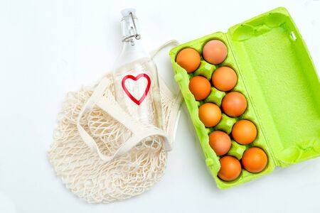 Reusable bottle and reusable mesh bag on white background. Sustainable lifestyle. Flat lay Imagens