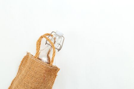 Bag of linen and reusable bottle on white background. Copy space