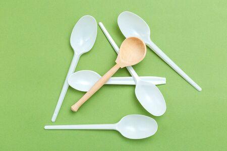 Alternative wooden spoon versus plastic on green background. Flat lay. Zero waste concept Imagens - 134805084