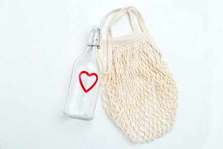 Reusable bottle and reusable mesh bag on white background. Sustainable lifestyle Imagens - 134805086