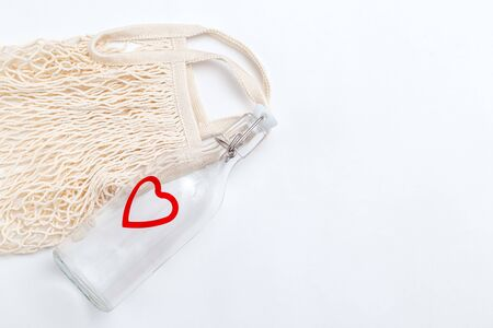 Reusable bottle and reusable mesh bag on white background. Minimalist concept. Copy space Imagens - 134805109