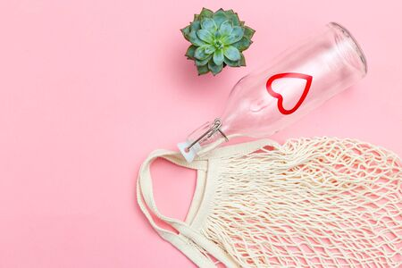 Reusable bottle and reusable mesh bag on pink background. Sustainable lifestyle. Copy space