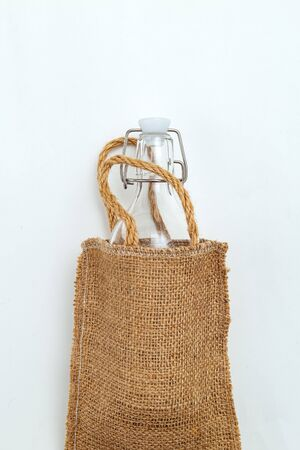 Bag of linen and reusable bottle on white background. Vertical