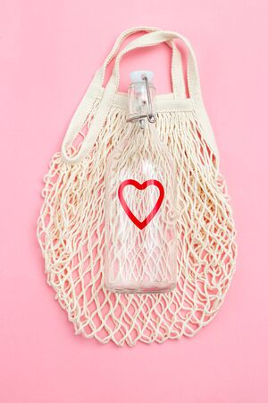 Reusable bottle on pink background. Glass bottle and mesh bag. Vertical photo Imagens - 134805117