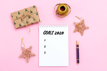 Goal list. Notepad  with pen and Christmas golden accessories on pink background. Christmas time