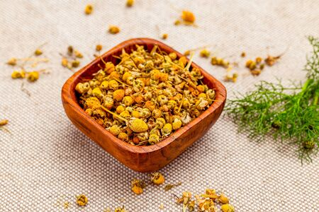 Dry chamomile herbs on linen background.  Healthy lifestyle. Natural ingredients