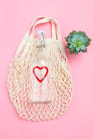 Reusable bottle and reusable mesh bag on pink background. Sustainable lifestyle. Succulents plants. Vertical
