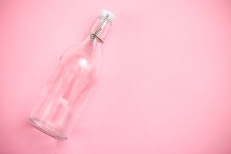 Reusable bottle on pink background. Glass bottle. Copy space. Retro
