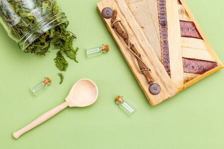 Dried mint, wooden spoon and notebook on a green background. Healthy lifestyle. Flat lay