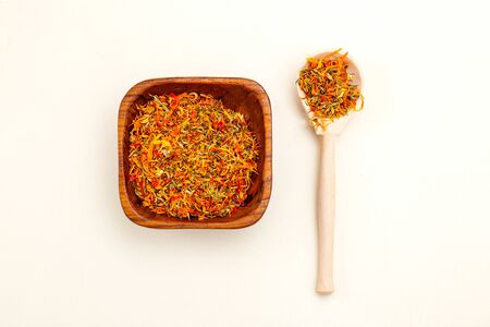Dried calendula in a wooden bowl and wooden spoon on a light background. Apothecary herbs