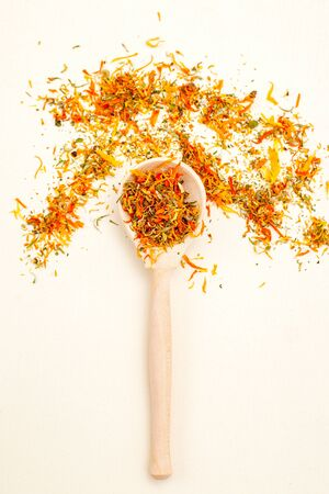 Dried calendula herbs and wooden spoon. Healthy lifestyle. Vertical photo