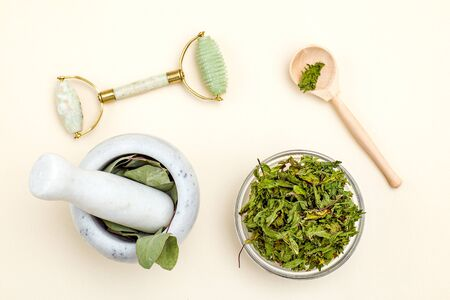 Dried herbs and face roller. Organic skin care. Sustainable lifestyle.