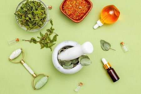 Dried herbs and face roller on green background. Organic skin care