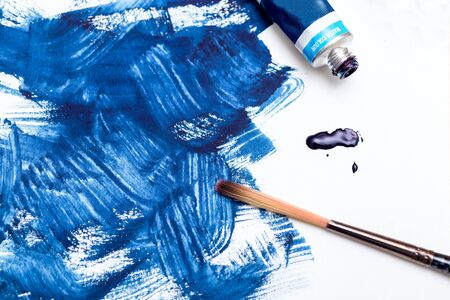 Tube of blue  paint and blue paint strokes on white background. Flat lay. Color 2020 Imagens - 136682099