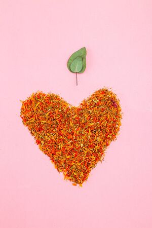 Dried calendula in the shape of a heart and eucalyptus leaf on a pink background. Vertical photo Imagens - 135228251