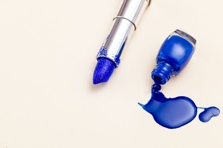 Lipstick with blue sparkles and blue nail polish. Color 2020. Copy space
